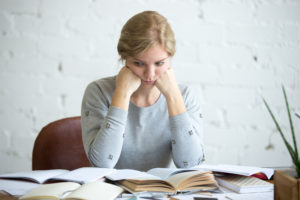 Portrait of a tired student woman sitting at the desk, lifestyle. Education concept photo