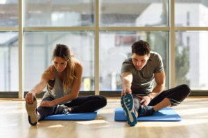 Young woman and man working out indoors. Two people streching their legs on the floor of a gym.