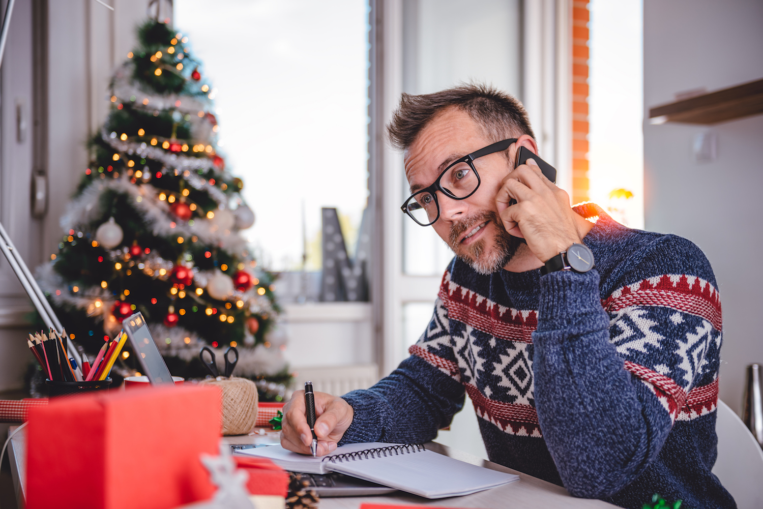 Men wearing blue sweater and eyeglasses talking on smart phone and writing notes