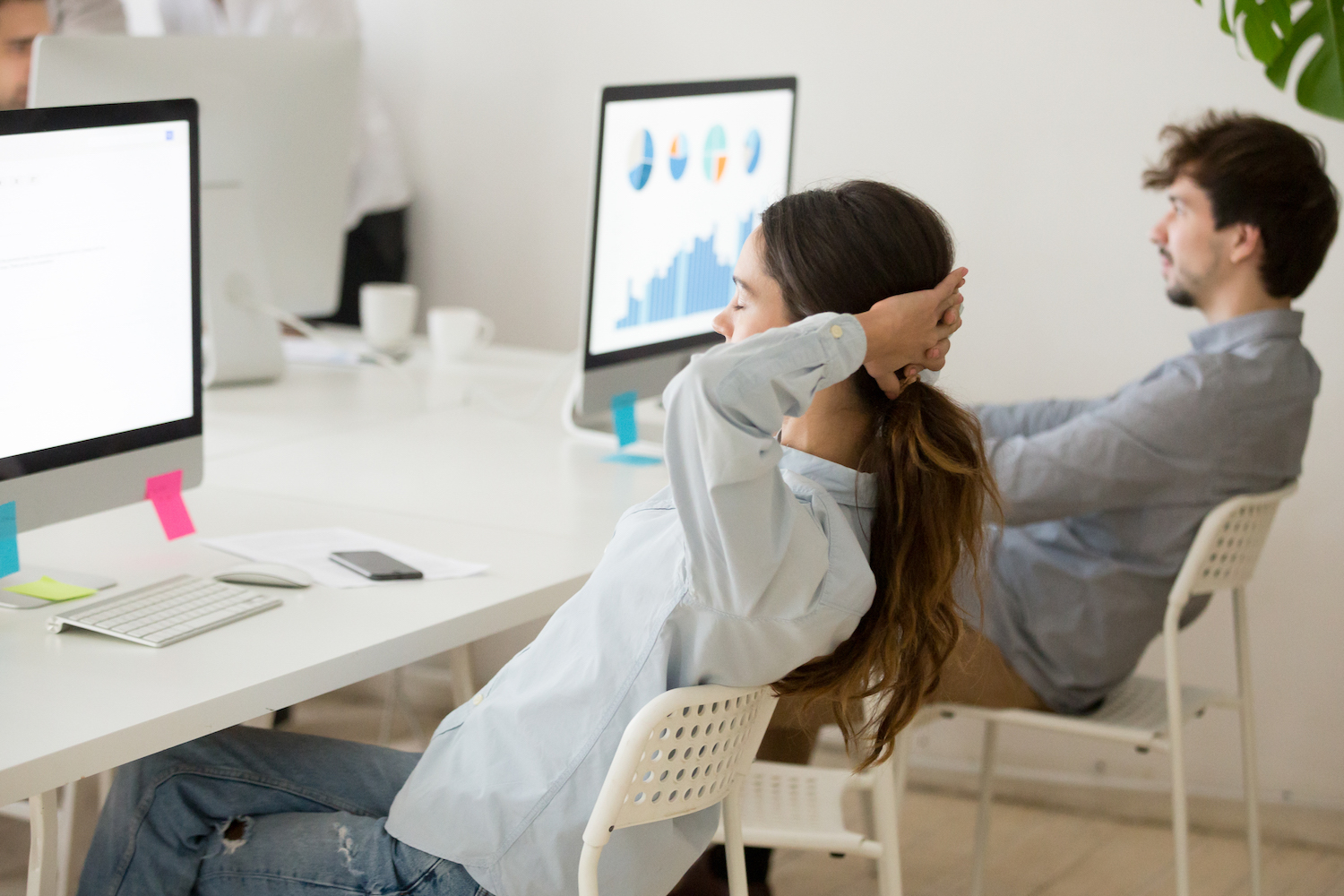 Female employee relaxing from computer work holding hands behind head